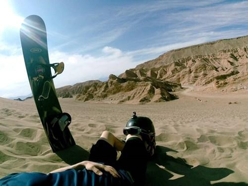 Snowboard stuck in sand